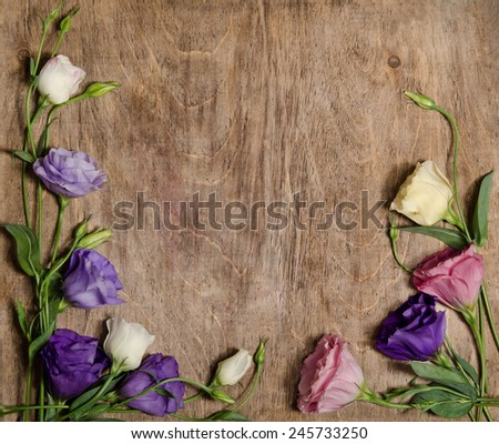 beautiful eustoma flowers with leafs and buds on wooden background located at the bottom  - stock photo