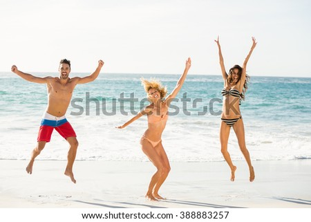 Beautiful excited friends jumping on the beach on a sunny day