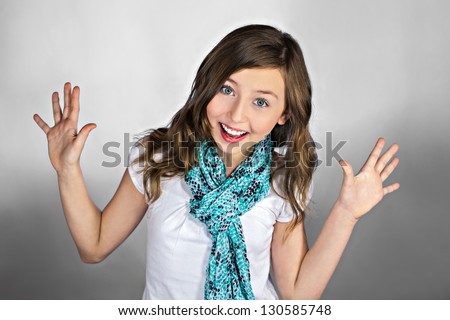 Beautiful excited teenage girl with hands up. Smiling and looking into the camera - stock photo