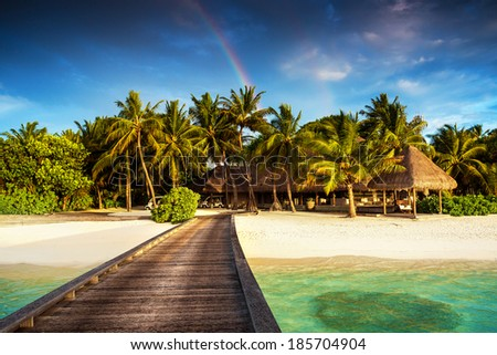 Beautiful exotic beach landscape, wooden pier on clear turquoise water, colorful rainbow over luxury island resort, summer vacation and holidays concept - stock photo