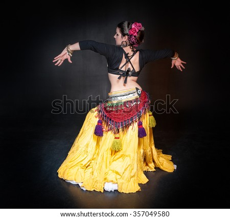 Beautiful exotic belly tribal dancer woman on black background
