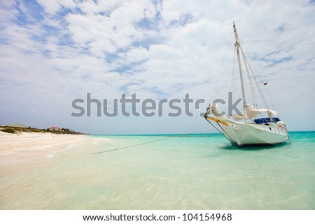 Beautiful exotic coast and luxury sail boat close to the shore - stock photo
