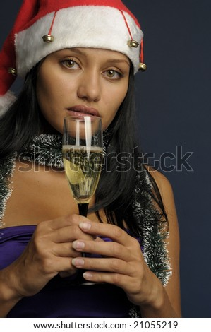 beautiful exotic woman in the red hat with the glass of champagne into Christmas