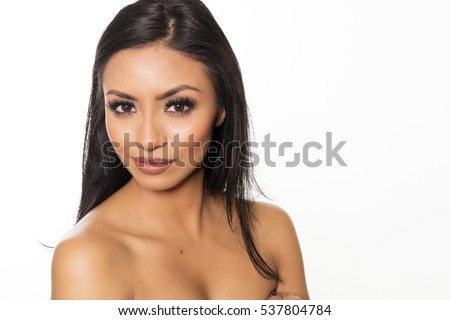 Beautiful exotic woman with dark hair, fresh glowing skin face and bare shoulders portrait.