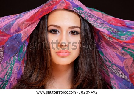 Beautiful exotic young woman wearing a colorful veil against a black background.