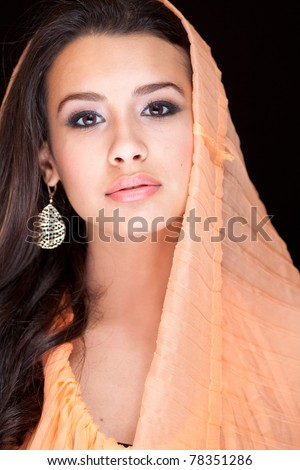 Beautiful exotic young woman wearing a veil against a black background.