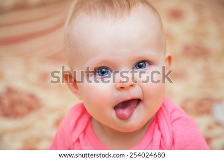 Beautiful expressive adorable happy cute laughing smiling baby infant face showing tongue - stock photo