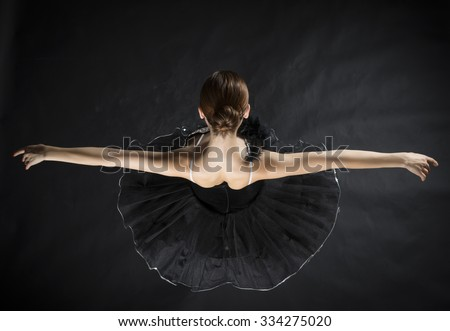 Beautiful expressive ballerina in the role of a black swan, making reverence, wearing black tutu and pointe shoes on black background - stock photo