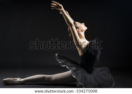 Beautiful expressive ballerina in the role of a black swan, wearing black tutu and pointe shoes on black background - stock photo
