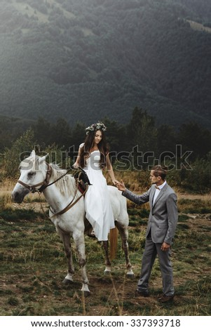 beautiful fabulous happy  bride riding a horse and stylish groom on the background of   the stunning mountains - stock photo