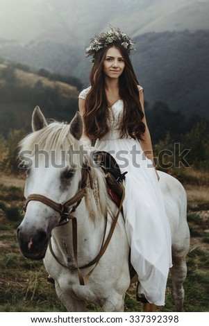 beautiful fabulous happy  bride riding a horse  on the background of   the stunning mountains - stock photo