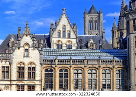 Beautiful facades of Gothic buildings in front of St Nicholas church tower, Ghent, Belgium - stock photo