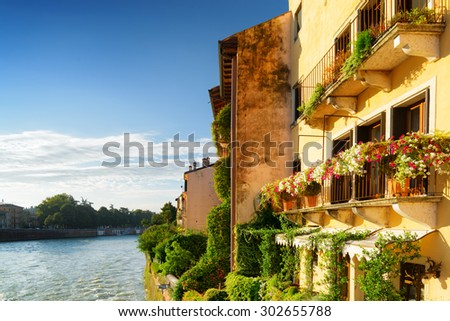 Beautiful facades of old houses decorated with flowers on waterfront of the Adige River in Verona (Italy) in morning sun. Verona is a popular tourist destination of Europe. - stock photo