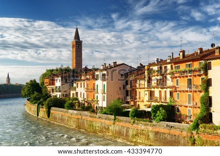 Beautiful facades of old houses on waterfront of the Adige River and bell tower of Santa Anastasia church in Verona, Italy. Verona is a popular tourist destination of Europe. - stock photo