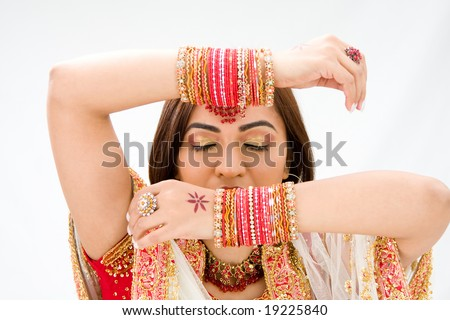 Beautiful face of a Bengali bride with her arms across her head covered with colorful bracelets and eyes closed, isolated - stock photo
