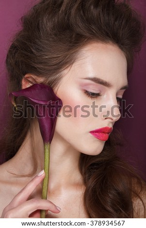 Beautiful face of a fashion model with blue eyes.Flower. Curly hair. Pink lips. Studio portrait. Warm skin. Spring look.