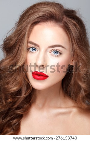 Beautiful face of a fashion model with red lips and blue eyes. Blonde curly hair. - stock photo