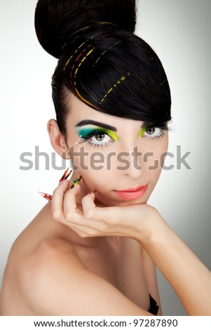 Beautiful face of a glamour woman with modern curly hairstyle, brightly makeup and big nails - stock photo