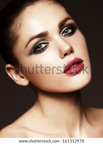 Beautiful face of a glamour woman with smoky eyes make up. Close-up beauty portrait of young beautiful woman. Shooted on black background - stock photo