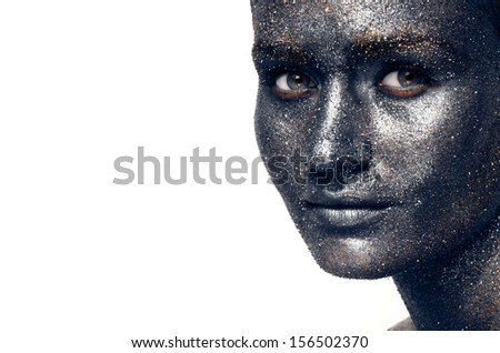 Beautiful face of a woman covered in glitter Close up of a woman's face covered in silver glitter