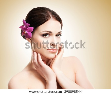 Beautiful face of a young and healthy girl with an orchid flower in her hair over yellow background - stock photo
