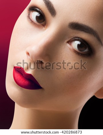Beautiful face of the woman of the brunette with brown eyes. Fashionable evening make-up, cosmetics. Red lips, dark shadows. The girl with ideal skin.