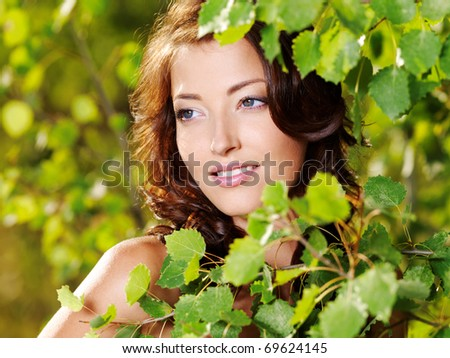 Beautiful face of the young sexy woman posing near the green tree on nature - stock photo