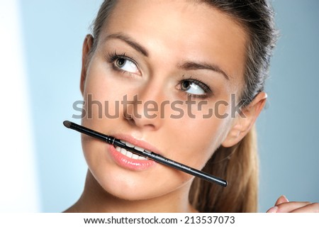 Beautiful face of young adult woman holing brush in mouth