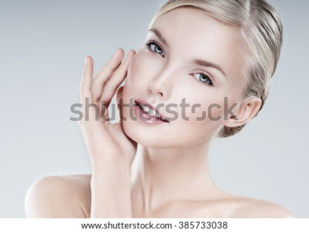 Beautiful face of young adult woman with clean fresh skin. - stock photo