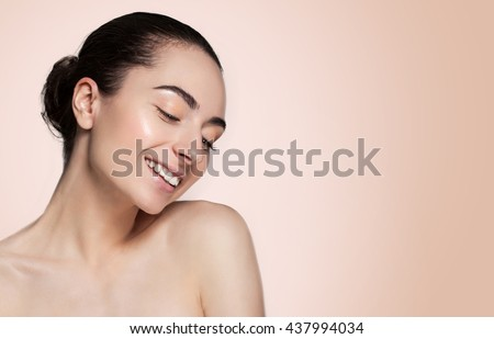 Beautiful face of young adult woman with clean fresh skin and bare shoulders on brown background. - stock photo