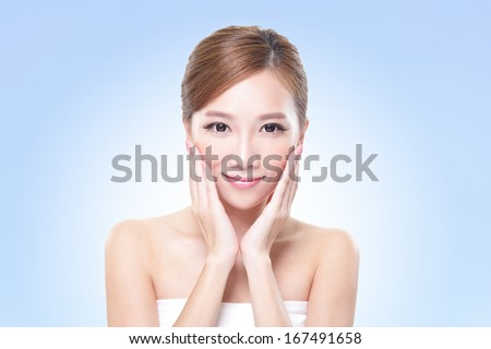 Beautiful face of young adult woman with clean fresh skin - isolated blue background, asian