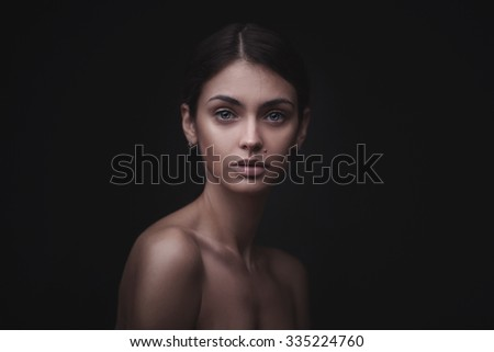 Beautiful face of young adult woman with clean fresh skin isolated on black background - stock photo
