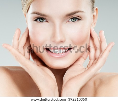Beautiful face of young adult woman with clean fresh skin. Smile. - stock photo