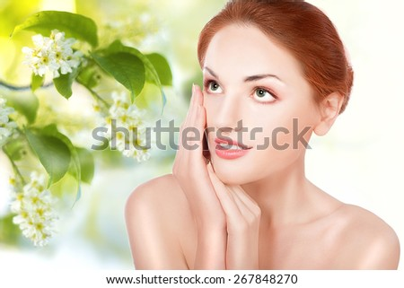 Beautiful face of young adult woman with clean fresh skin. Spring background - stock photo