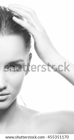 Beautiful face of young caucasian brunette woman with natural lips, make-up and blue eyes isolated on white. Touch her head. Perfect skin. Studio portrait. Black and white - stock photo