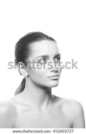 Beautiful face of young caucasian brunette woman with natural lips, make-up, perfect skin and blue eyes look up. Isolated on white background. Studio portrait. Black and white