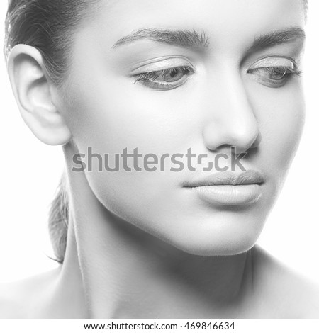 Beautiful face of young caucasian brunette woman with natural lips, make-up, perfect skin and blue eyes isolated on white. Studio portrait. Black and white