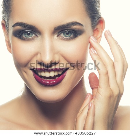 Beautiful face of young caucasian brunette woman with red glossy  lips, intensive make-up, perfect skin and blue eyes isolated on white touch her skin. Studio portrait. Toned