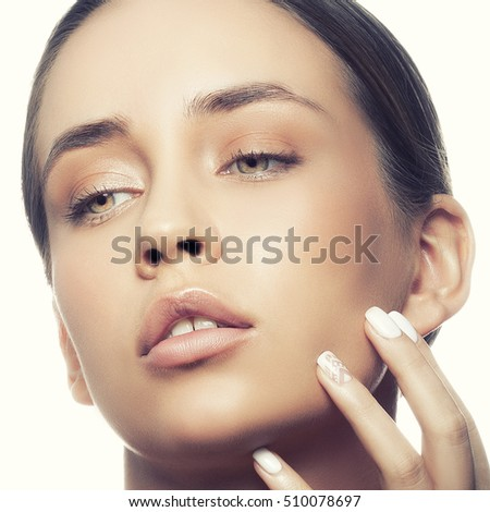 Beautiful face of young caucasian girl with natural make-up, perfect skin and green eyes isolated on white background. Studio portrait. Toned