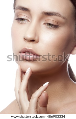 Beautiful face of young caucasian girl with natural make-up, perfect skin and green eyes touch her skin isolated on white background. Studio portrait.