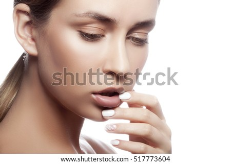 Beautiful face of young caucasian girl with natural make-up, perfect skin and green eyes touching her lips isolated on white background. Studio portrait.