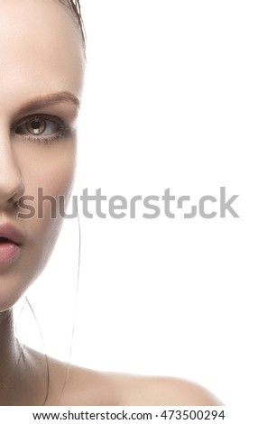 Beautiful face of young caucasian woman with natural make-up, perfect skin, wet hair and green eyes isolated on white. Studio portrait.