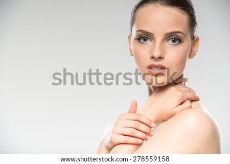 Beautiful face of young woman with clean fresh skin on grey background. - stock photo