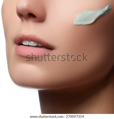 Beautiful face of young woman with cosmetic cream on a cheek. Skin care concept. Closeup portrait on beige background. Close-up young beautiful face of girl applying moisturize cream - stock photo