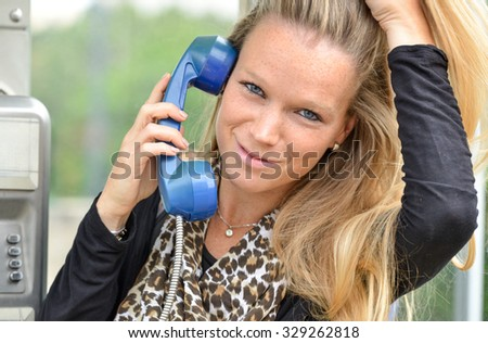 beautiful fair hair woman talking on the phone in a retro phone booth