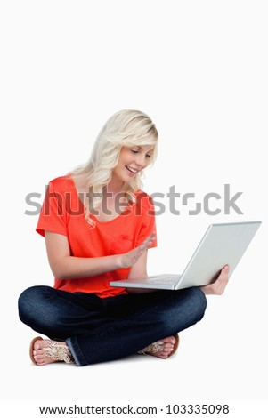 Beautiful fair-haired woman waving her right hand in front of her new grey laptop - stock photo