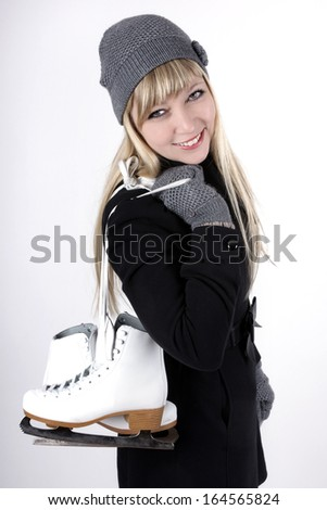 Beautiful fair haired young woman with ice skates - stock photo