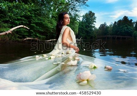 Beautiful fairy girl in a long white dress and flowers standing in the river in a forest - stock photo