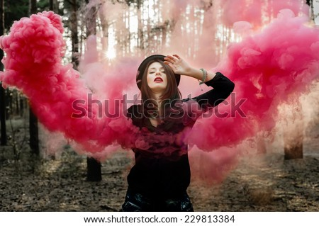 Beautiful fairy with pink smoke wings in the forest. - stock photo