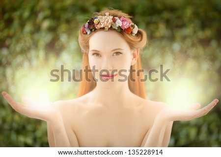 Beautiful fairy woman with glow in hands on natural green background